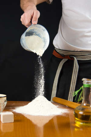 Man pouring flour from the measure bowl on the table