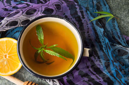 Cannabis herbal tea with lemon on purple fabric Banco de Imagens