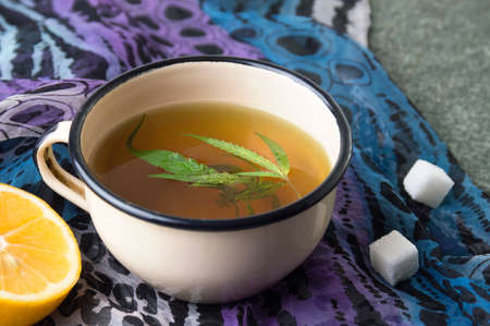 Cannabis herbal tea with lemon on stone table