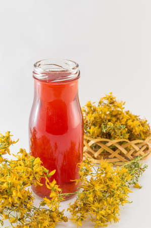 Saint Johns wort oil in a bottle and dried flowers