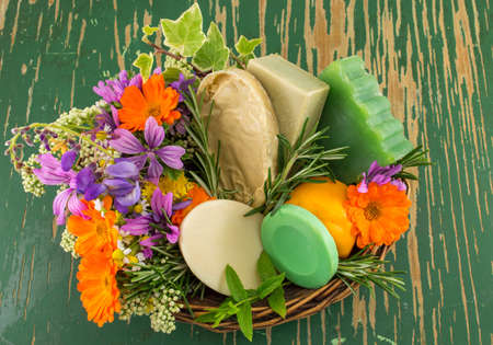 Herbal soaps and fresh spring flowers in a bowl