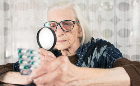 Senior woman reading pill name with magnifying glass at home