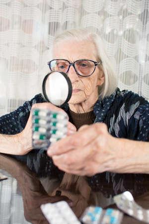 Oma met vergrootglas om medicijnnaam te bepalen Stockfoto