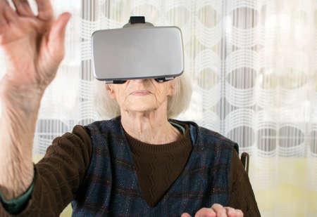 Senior woman using virtual reality goggles at home