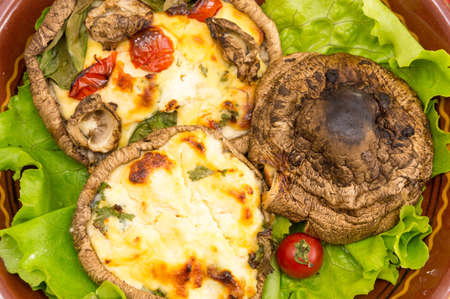 egg stuffed mushrooms on a brown plate with cherry tomatoes Stock Photo