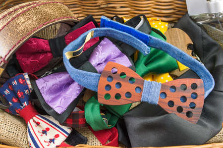 Bunch of bow ties and male accessories in a wicker box