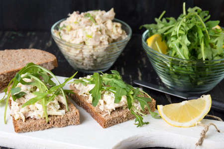 sandwitch: Chicken salad and arugula sandwich on wooden board Stock Photo