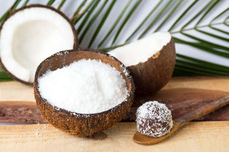 Coconut powder in a natural shell with leaves Фото со стока