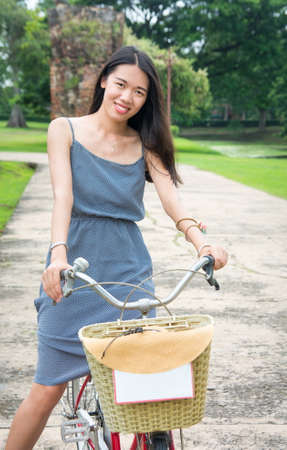 museum visit: Girl riding bicycle in Ayutthaya city park in Thailand