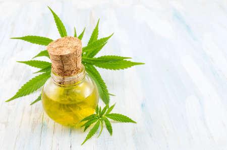 plante de marijuana et huile de cannabis sur une table en bois