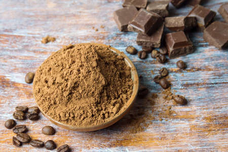 Cacao powder in a bowl with chocolate pieces and cinnamon
