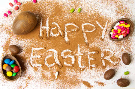 Happy Easter written in cacao powder with chocolate eggs Stock Photo