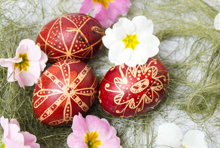 Easter eggs decorated with wax and flowers on straws