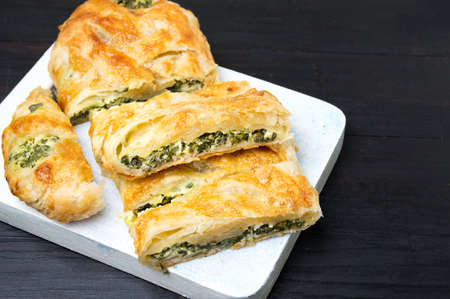 Spinach and cheese pie slices on a wooden tray