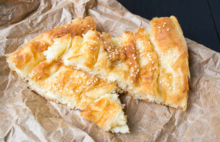 Cheese pie covered with sesame on wrapping paper Stock Photo