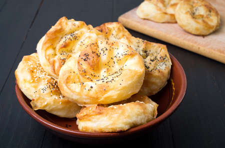 Homemade cheese pie rolls covered with sesame on a plate