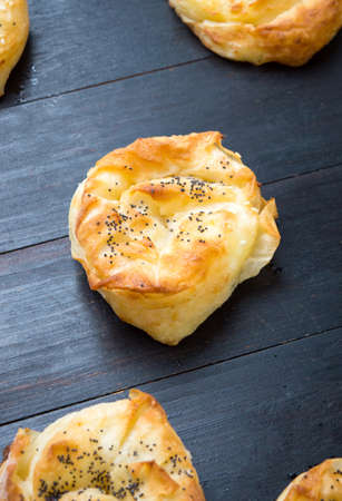 Homemade cheese pie rolls covered with sesame on a table Stock Photo
