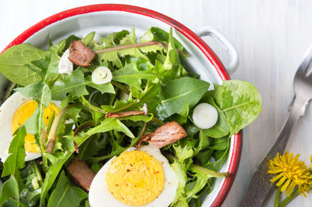 Dandelion egg salad with onions and cheese in a bowl