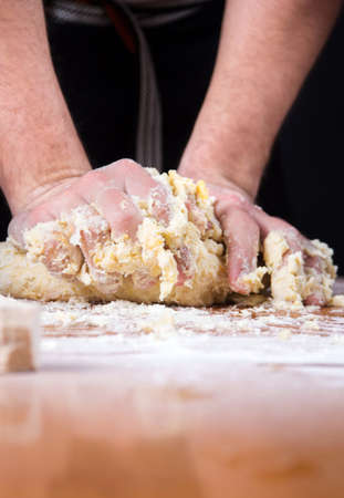 unify: Male baker kneading dough on a flour covered table