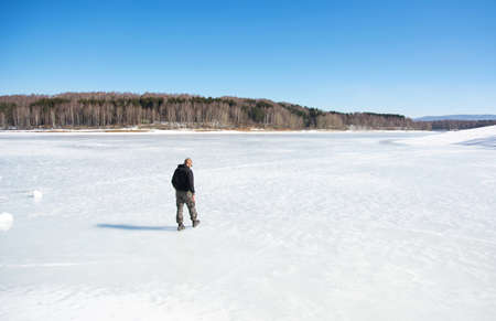 Man walking on the frozen lake surface Stock Photo