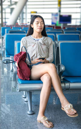 Girl sleeping in the airport waiting hall Stock Photo