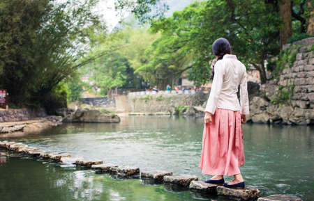 Girl walking on small stone bridge in the river Stock Photo