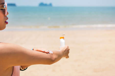 moisturize: Girl applying sun lotion on her hands at the beach