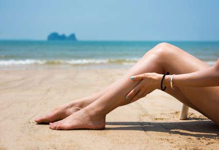 Girl applying sun lotion on her leg