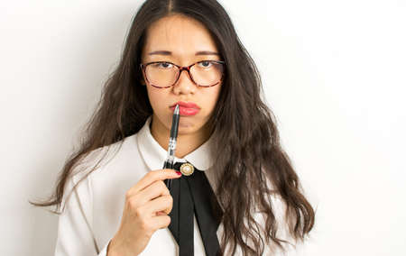 Tired asian businesswoman with glasses holding a pen