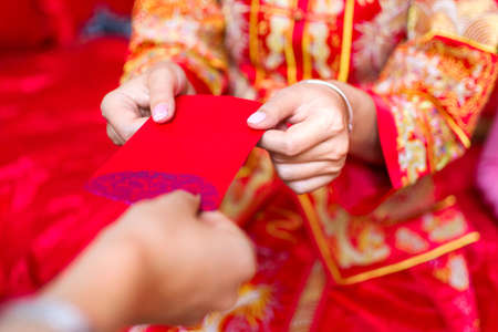 Chinese bride giving red pocket lucky money in the wedding Stock Photo