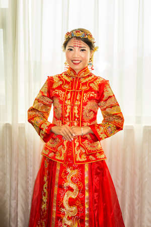 Chinese bride in traditional red wedding dress portrait Stock Photo