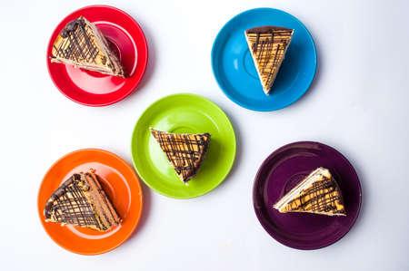 paletas de caramelo: Rodajas de pastel de caramelo servidas en platos de colores Foto de archivo