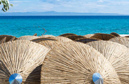 Straw umbrellas at the beach with seaside view