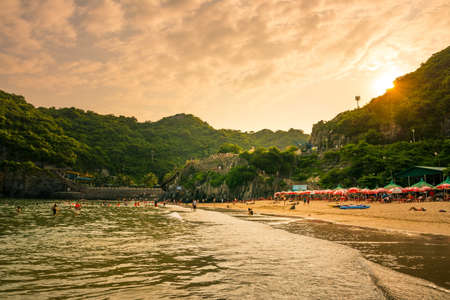 CAT BA, VIETNAM - MAY 25, 2017: Cat ba island city beach Cat co 1 with tourist sunbathing on the sand and calm seaside at sunset. Cat co beach number 1 is the biggest beach on the island