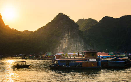 CAT BA, VIETNAM - MAY 27, 2017: Fisherman village of houses on water and boats near Cat ba island at sunset