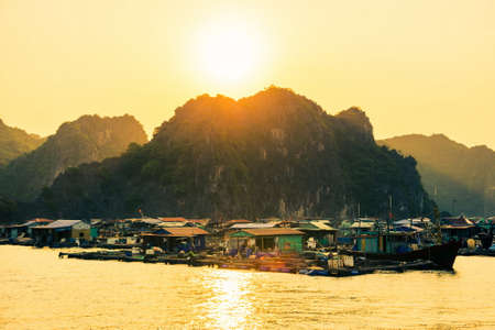 enviroment: CAT BA, VIETNAM - MAY 27, 2017: Fisherman village of houses on water and boats near Cat ba island at sunset