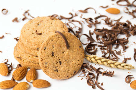 Integral cookies with almonds and chocolate pieces on white