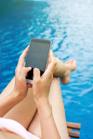 Girl using phone by the swimming pool, first person Stock Photo