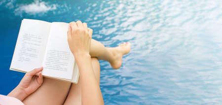 Girl reading a book by the swimming pool. First person