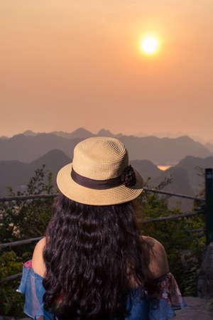 Girl enjoying sunset view from Cannon fort viewpoint in Cat ba, Vietnam