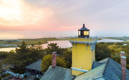 wildwood: Lighthouse and horizon over seaside at sunset, aerial view Stock Photo