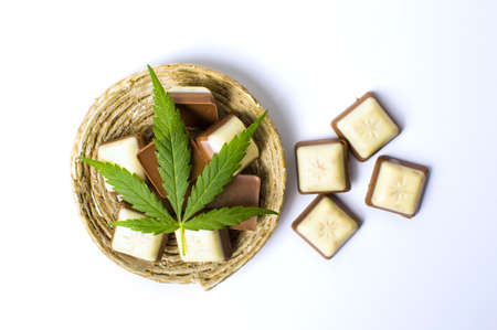 legalization: Marijuana leaf on top of chocolate pieces isolated
