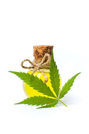 Cannabis oil and marijuana leaf isolated on white