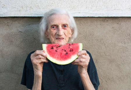 ninety: Senior woman eating watermelon fruit in the backyard Stock Photo
