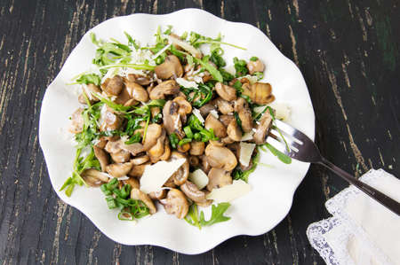 Fried mushrooms with vegetables on a white plate Imagens