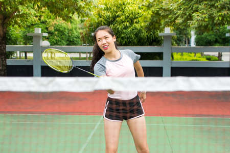 Asian girl playing badminton on the outdoors court Foto de archivo