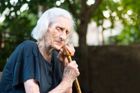 Senior woman crying with a walking cane outdoors