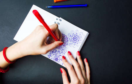 Female drawing flower shapes in a notebook