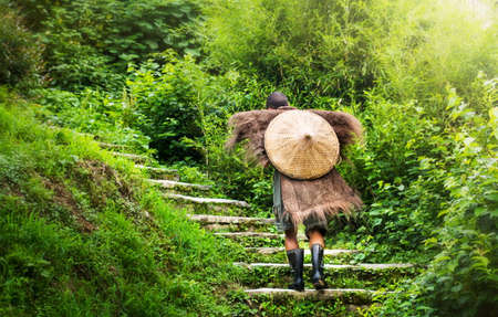 Chinese farmer wearing an antique raincoat walking up stairs