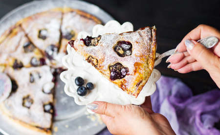 Female serving blueberry fruit sweet pie first person